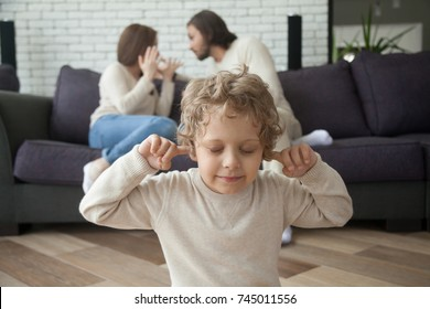 Little boy puts fingers in ears not to hear parents fighting at background, upset tired son suffering from mom and dad arguing, parental conflicts hurt kid, family divorce effect on children concept