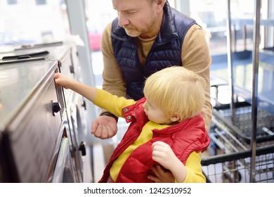 Little boy puts token in the washing machine in the public Laundry. Family in public Laundry