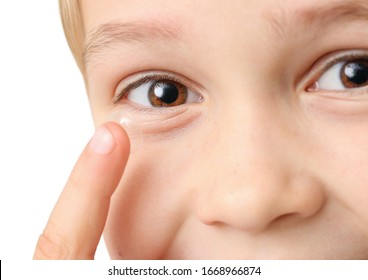 Little boy putting in contact lens, closeup