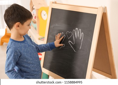 Little boy putting his palm on drawing at child psychologist's office. Autism concept