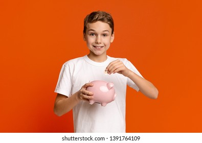 Little boy putting pocket money in piggy bank, raising funds for desired toy, orange studio background