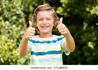 A little boy is putting up their thumbs in the air in a garden