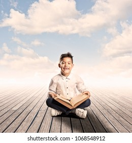 little boy reading a book on a wharf