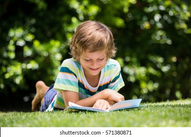 A little boy is reading a book on the grass