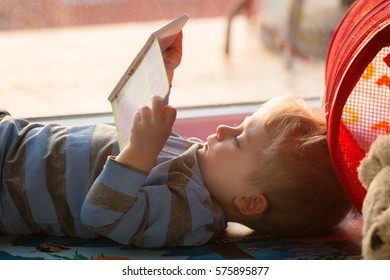 Little boy reading a book on the floor