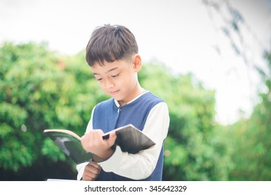 Little boy reading book in the park