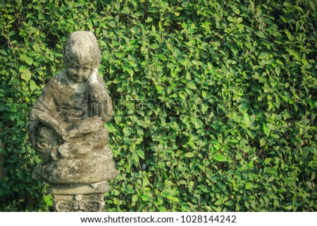 Little Boy Reading Book Statue In The Garden With Copy Space
