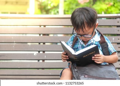 Little boy reading Holy Bible. Christianity concept. Faith hope love concept.
