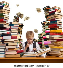 Little boy is reading interesting book. High stacks of books are on the table near him.