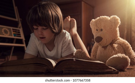 Little boy reading an old book with his teddy bear