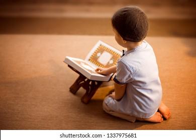 little boy reading the Quran