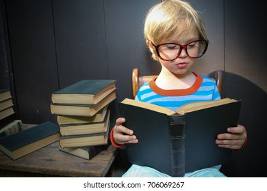 A little boy is reading a stack of old books. He has a pair of big glasses on.