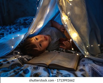 Little boy reads book. Toddler plays in tent made of linen sheet on bed. Cozy evening with favorite book.