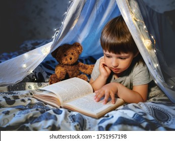 Little boy reads book. Toddler plays in tent made of linen sheet with light bulbs on bed. Cozy evening with favorite book.