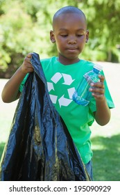 Little boy in recycling tshirt picking up trash on a sunny day