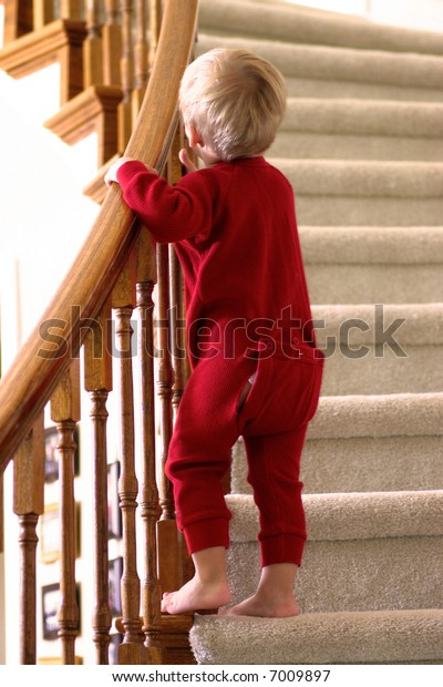 Little boy in red Christmas long john pajamas heading upstairs