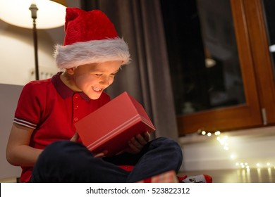 Little boy in red Santa Claus cap opening a Christmas gift