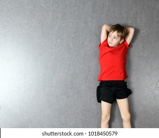 little boy in red shirt lying on the floor and relaxing