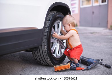 Little boy in red shorts changes a wheel at the car. Nearby tools for repair and cleaning of the car. Concept of a profession