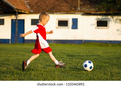 The little boy in red soccer dress is playing soccer on playing field outdoors.