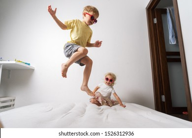 A little boy in red sunglasses and a yellow skirt jumps on a white mattress. Studio portrait on a white background.