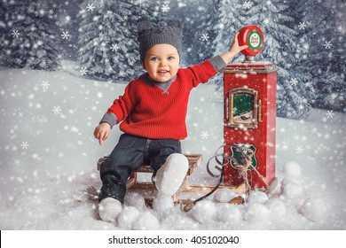 little boy in red sweater sitting on sled in the winter forest fairy and playing with