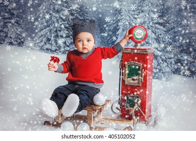 little boy in red sweater sitting on sled in the winter forest fairy and playing with children's gas station