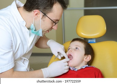 little boy in a red sweater went to the dentist in the dental chair sits next to a doctor to do the dentist to see if his teeth were okay / little boy at the dentist