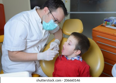 little boy in a red sweater went to the dentist in the dental chair sits next to a doctor to do the dentist to see if his teeth were okay/little boy in a red sweater went to the dentis