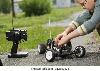 Little boy repaire the radio control car outdoor near field