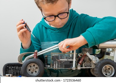 little boy repairing a model radio-controlled car