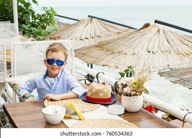 Little boy in restaurant on sea beach, no one else, white chairs and straw umbrellas, summer spring morning, sunny day, ocean sealine, resort, vacation