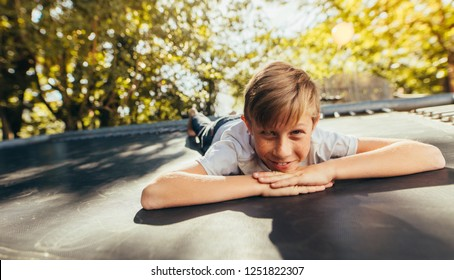Little boy resting on trampoline after playing outdoors. Kid lying on front on a trampoline and smiling.