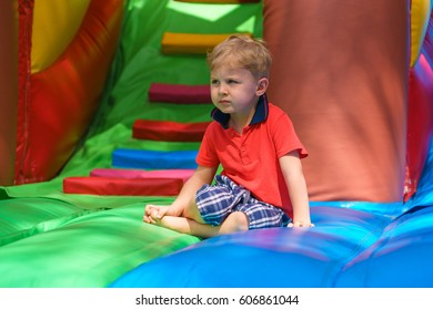 Little boy is resting, sitting on a children's inflatable trampoline. He looks into the distance. Bright and motley colors. Sunny day.