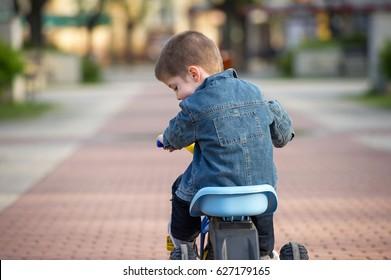 little boy ride toy motorcycle on sidewalk