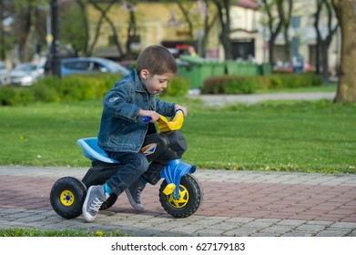 little boy ride toy motorcycle on sidewalk