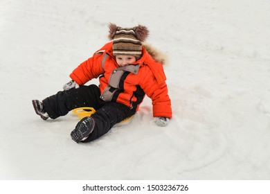 Little boy rides on an ice-boat from a snow slide. Sledding snow saucer - winter childrens fun. Winter activity.