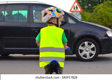 Little boy riding a bike on the road. Child is wearing reflective vest and helmet because of safety. Driving car in front of him. Sign of Children going to or from school in the background.