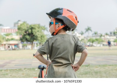 Little boy riding a bike in the park. Child on bicycle. Looking forward ahead.