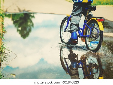little boy riding bike in water puddle