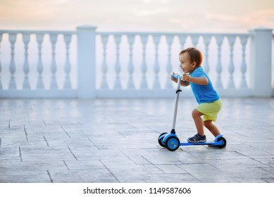 Little boy riding a blue kick scooter along white balustrade on the embankment. Happy child in shorts and shirt with a scooter. Dynamics, activity and motion concept. Room for text