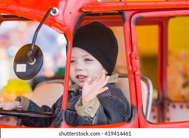 Little boy riding a bus in amusement park