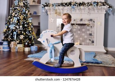 Little boy riding a cardboard horse near the Christmas tree