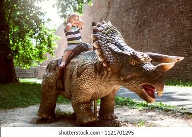 Little boy riding dinosaur in dino park