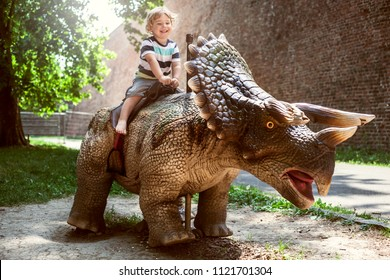 Little boy riding dinosaur in dino park