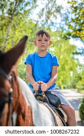 Little boy riding a horse peering over the top of its ears at the camera with a smile as he rides along a leafy road