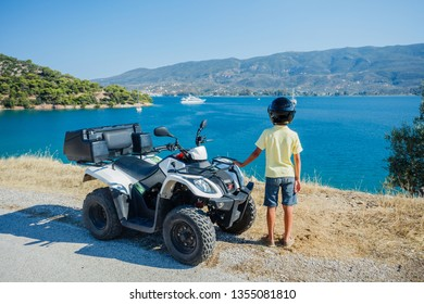 Little boy riding and looking quad bike on Greece island. Cute child on quadricycle. Motor cross sports on Greece island. Kids summer vacation activity.