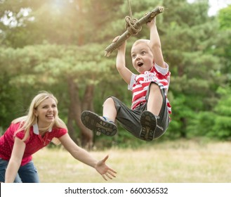 Little boy riding on a makeshift swing in the woods.Mom looks at the flight of a little son.
