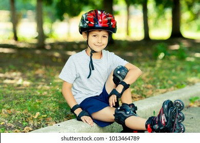 Little boy riding on rollers in the summer in the Park. Happy child in helmet learning to skate.