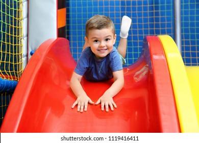 Little boy riding on slide in entertainment center